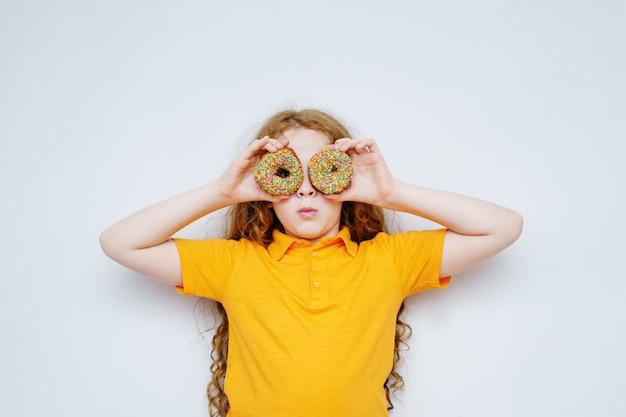 Petite fille s'amuser avec les yeux de beignets. Photo Premium