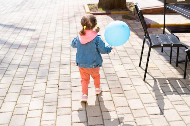 La petite fille s'enfuit de ses parents avec un ballon gonflable à la main. Photo Premium