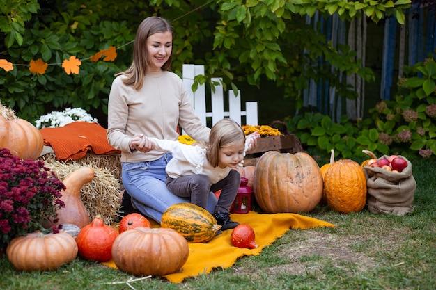 Petite fille et sa mère avec des citrouilles Photo Premium