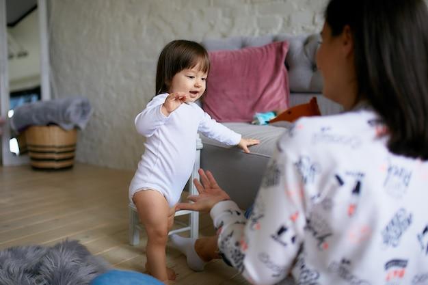 Petite fille et sa mère habillées dans un style décontracté s'amusent à jouer au sol Photo gratuit