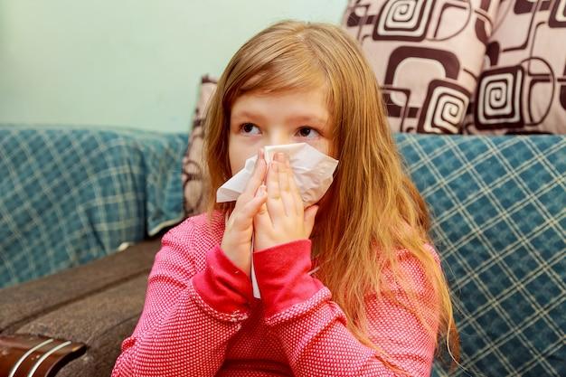 Petite fille se mouche dans un mouchoir en papier Photo Premium