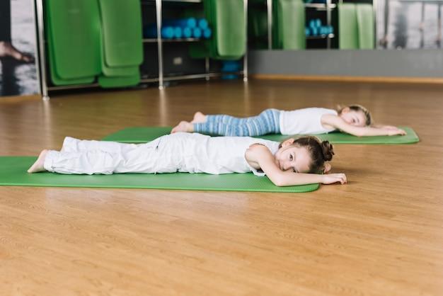 Petite fille se reposant sur le tapis après l'exercice Photo gratuit