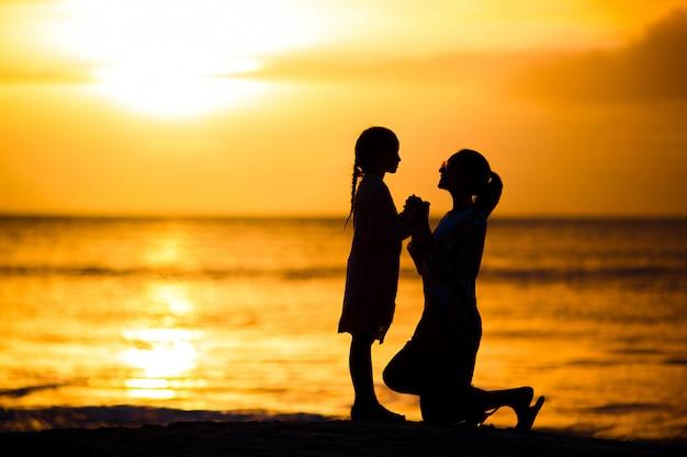 Petite fille et silhouette de mère heureuse au coucher du soleil à la plage Photo Premium