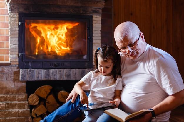 Petite fille et son grand-père assis sur un canapé dans le salon décoré pour noël Photo Premium