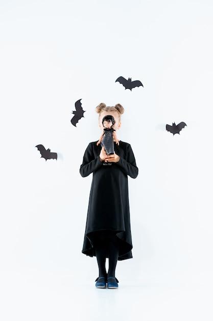 Petite Fille Sorcière En Robe Longue Noire Et Accessoires Magiques. Halloween Photo gratuit