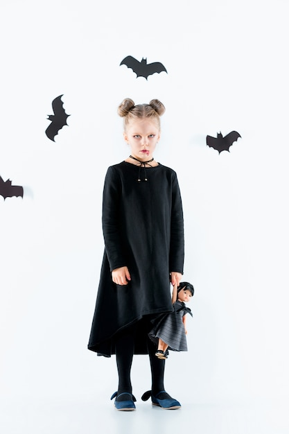 Petite Fille Sorcière En Robe Longue Noire Et Accessoires Magiques Photo gratuit