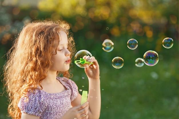 Petite fille soufflant des bulles de savon au printemps en plein air. Photo Premium