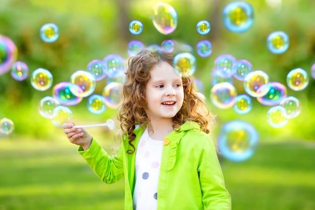 Une petite fille soufflant des bulles de savon, portrait de printemps beau bébé frisé. Photo Premium