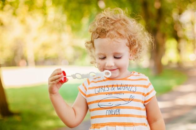 Petite fille soufflant des bulles de savon Photo Premium