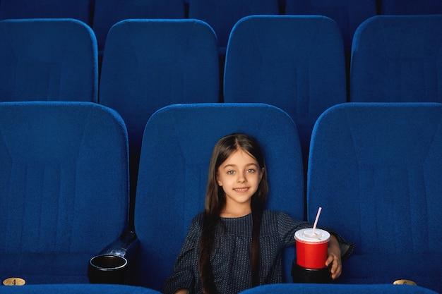 Petite Fille Souriante Assise Dans Un Cinéma Vide. Photo Premium