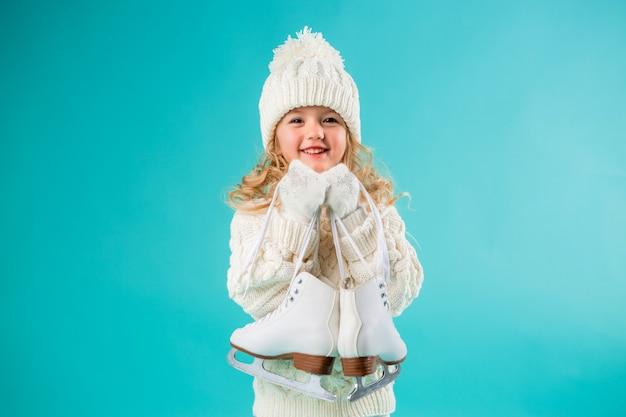 Petite fille souriante dans un chapeau blanc d'hiver et un pull, tenant des patins Photo Premium