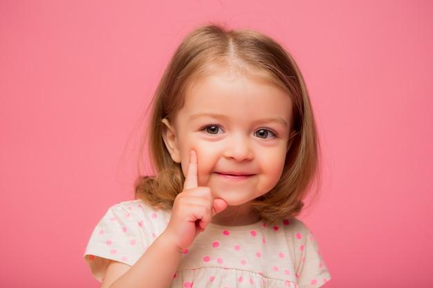 Petite fille souriante sur fond rose Photo Premium