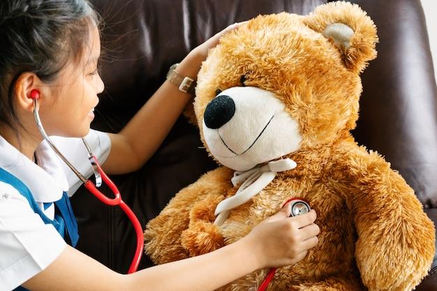 Petite fille souriante et jouant au docteur avec l'ours brun et le stéthoscope. enfant et soins de santé Photo Premium
