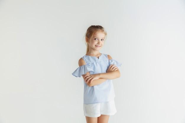 Petite Fille Souriante Posant Dans Des Vêtements Décontractés Sur Fond De Studio Blanc Photo gratuit