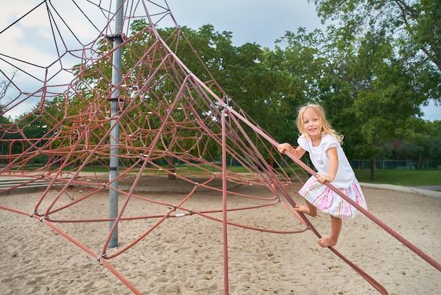 Petite Fille Souriante à La Recherche, Petit Enfant Jouant Sur Un Filet D'escalade. à L'extérieur Par Une Journée D'été Ensoleillée. Photo Premium