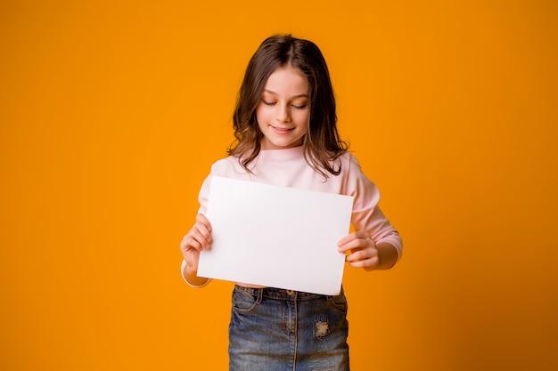 Petite fille souriante tenant une feuille blanche sur un fond jaune Photo Premium