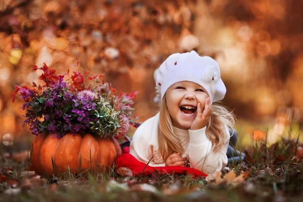 Petite fille sourit et se couche sur les feuilles d'automne Photo Premium