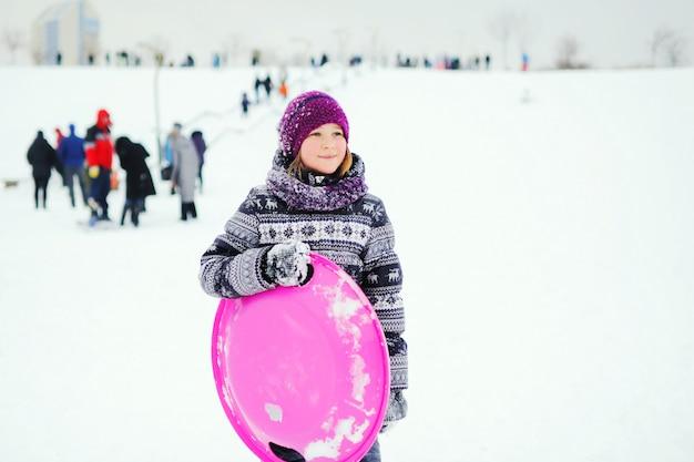 Une petite fille en survêtement d'hiver avec un imprimé scandinave tient une luge de glace et sourit contre une pente enneigée. divertissement d'hiver Photo Premium