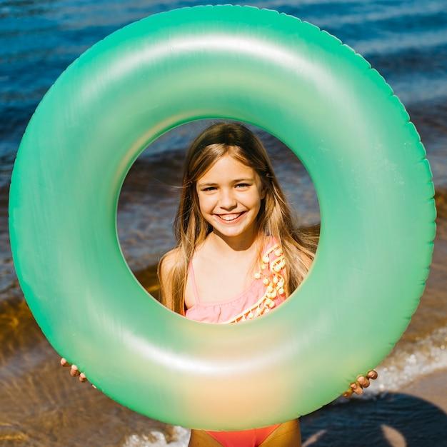 Petite fille tenant un anneau de natation gonflable Photo gratuit