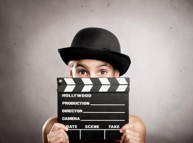Petite fille tenant un conseil d'administration de film battant sur un fond gris Photo Premium