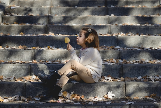 Petite fille tenant une feuille assis sur les escaliers Photo gratuit