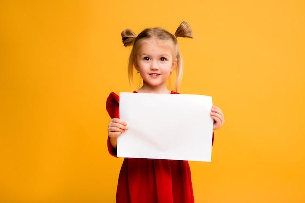 Petite fille tenant une feuille blanche. Photo Premium