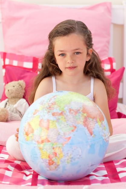 Petite fille tenant un globe terrestre Photo Premium