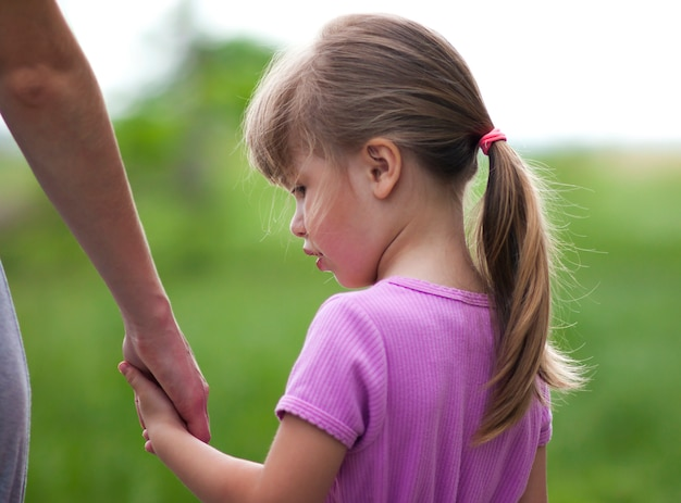 Petite fille tenant la main de sa mère. notion de relations familiales. Photo Premium