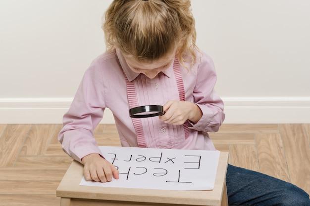 Petite Fille Tenant Un Morceau De Papier Avec Un Mot Tech Expert. Photo Premium