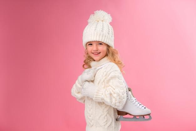 Petite fille tenant des patins. isoler sur le mur rose, espace pour le texte. Photo Premium