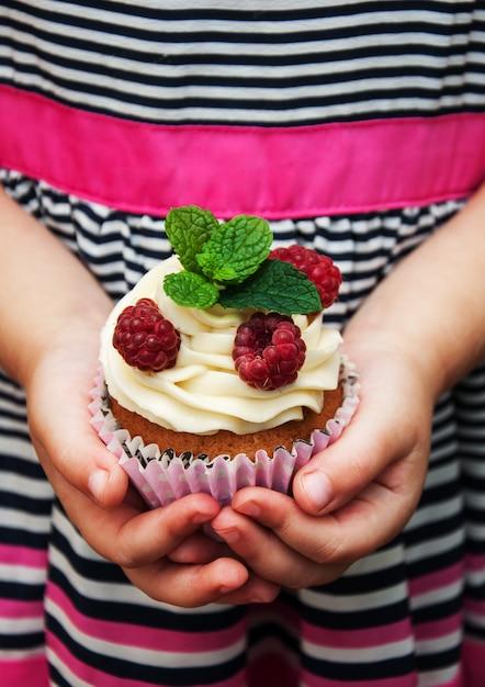 Petite fille tenant un petit gâteau Photo Premium