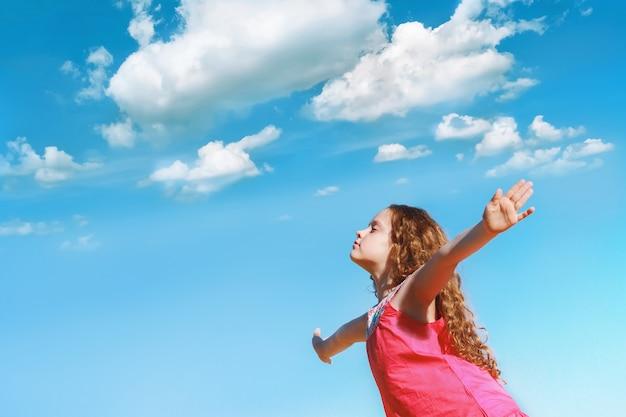 La petite fille tendit les bras et ferma les yeux, profitant de l'air frais. Photo Premium