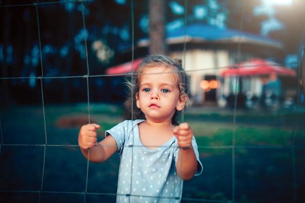 La petite fille tient la clôture à deux mains et regarde la caméra à travers la grille Photo Premium