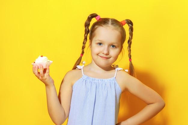 La petite fille tient un gâteau. Photo Premium