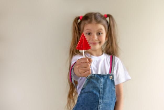 Une Petite Fille Tient Une Sucette Rouge Dans Sa Main. Photo Premium