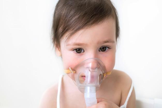 La petite fille traite la toux et le nez qui coule. la fille est assise avec l'inhalation Photo Premium
