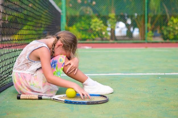 Petite fille triste sur un court de tennis Photo Premium