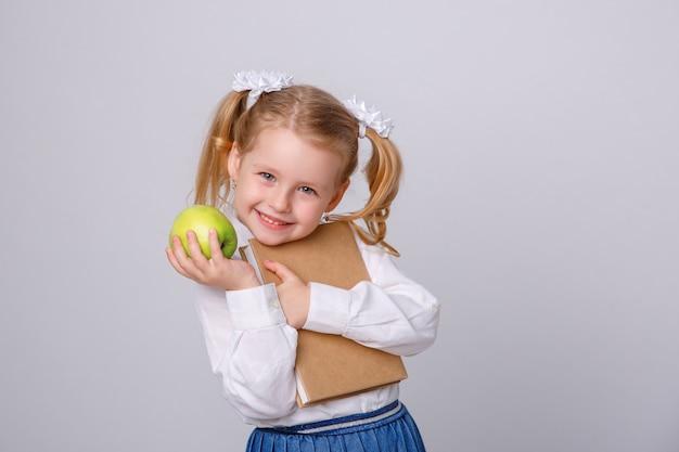 Petite fille en uniforme d'école sur fond blanc, lisant un livre Photo Premium