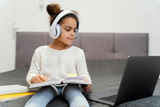 Petite Fille Utilisant Un Ordinateur Portable Et Des écouteurs Pour L'école En Ligne Photo gratuit