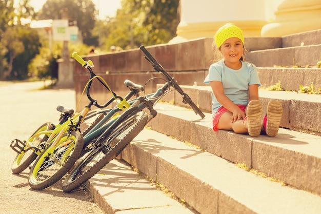 Petite fille à vélo dans une ville Photo Premium