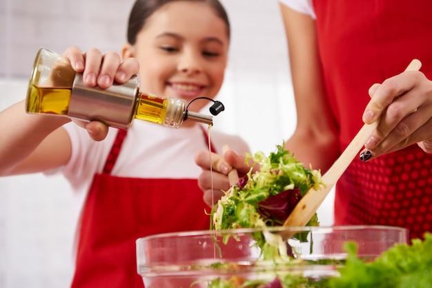 Petite fille verse de l'huile d'olive dans une salade de cuisine. Photo Premium