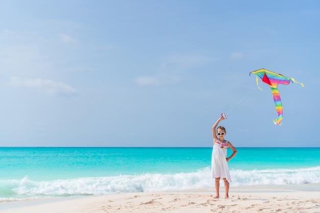 Petite fille voler un cerf-volant sur la plage Photo Premium