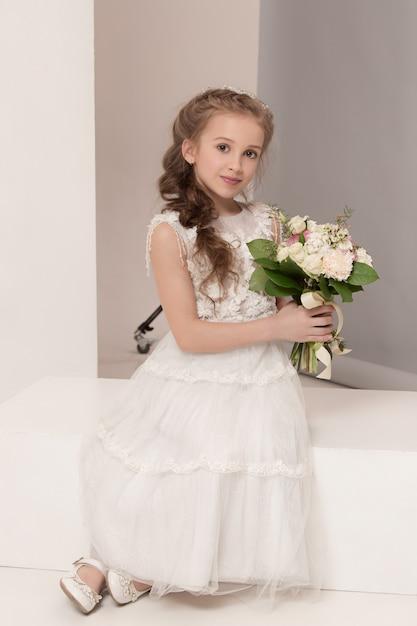 Petite Jolie Fille Avec Des Fleurs Vêtues De Robes De Mariée Photo gratuit