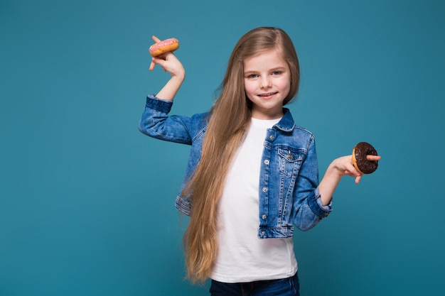 Petite jolie fille en veste de jean avec de longs cheveux bruns tenir doughnust Photo Premium