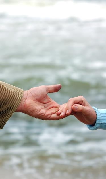 Petite main donnant une poignée de main à une grande main Photo gratuit