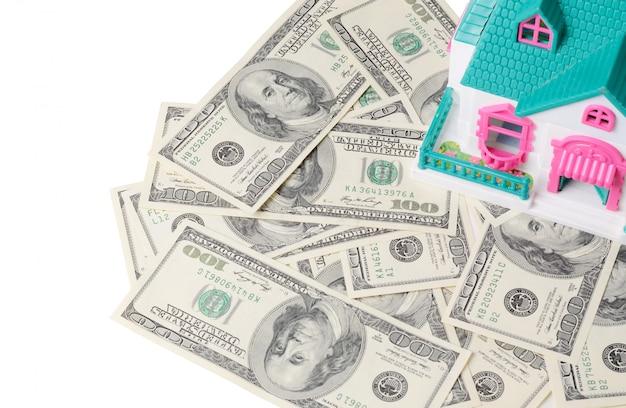 Petite maison de jouet debout sur des billets de cent dollars Photo Premium