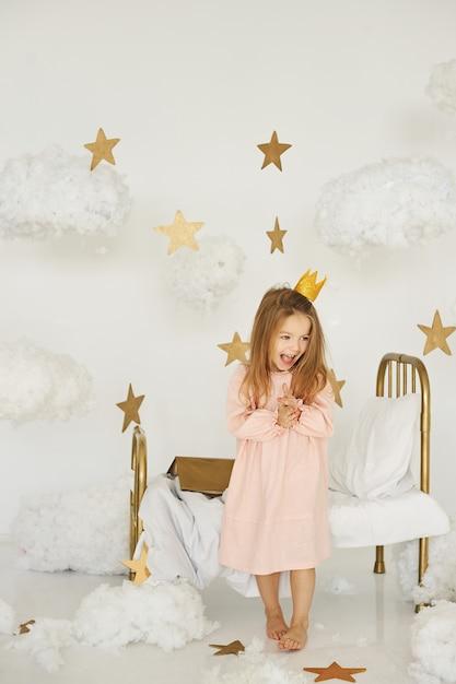 Petite princesse avec une baguette magique sur un lit dans un nuage sur fond blanc Photo Premium