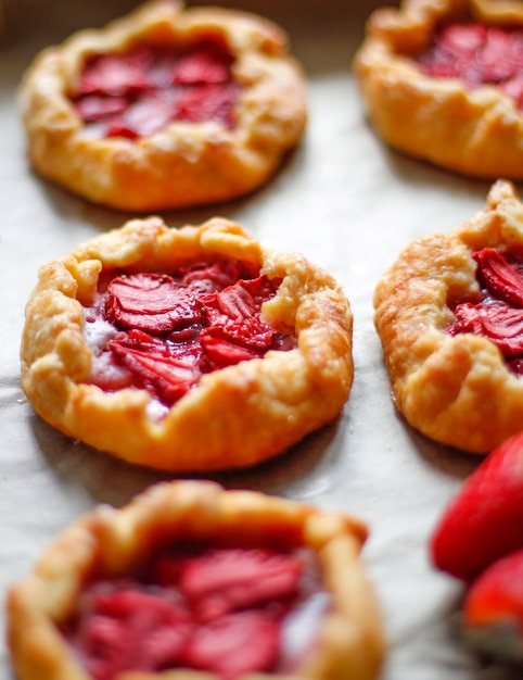 Petite tarte rustique à la galette aux fraises avec du sucre en poudre sur le plateau du four Photo gratuit