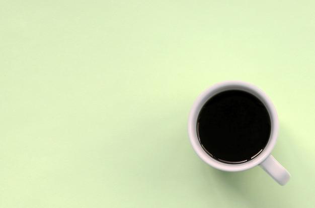 Petite tasse à café blanche sur fond de texture de papier de couleur mode citron vert pastel Photo Premium