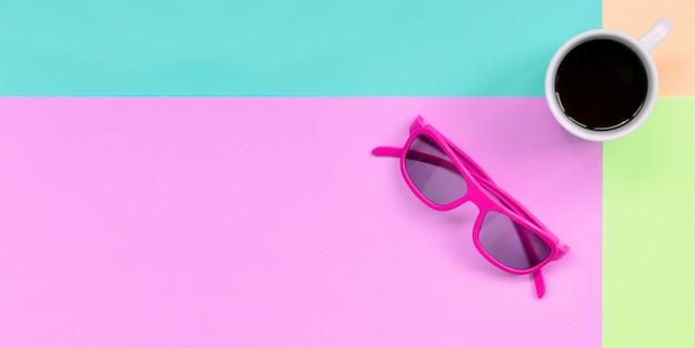 Petite tasse à café blanche et lunettes de soleil roses sur fond de couleurs rose pastel, bleues, corail et citron vert Photo Premium